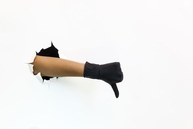 Een vrouwelijke hand in een zwarte latexhandschoen door gescheurd papier op een witte achtergrond toont
