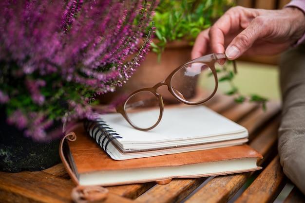 Een vrouwelijke hand met een bril buiten op het terras, thuiskantoorconcept