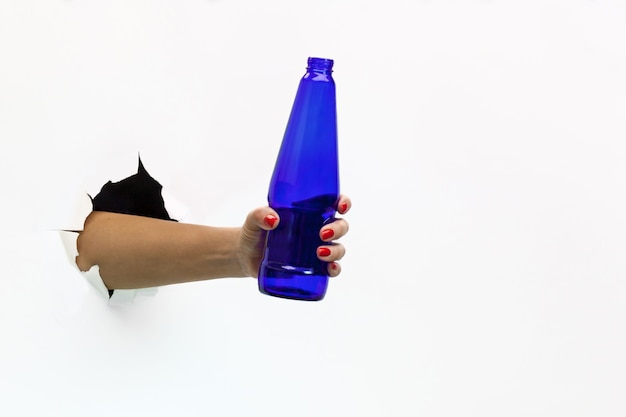 Een vrouwelijke hand met een rode manicure door gescheurd wit papier houdt een blauwe bierfles vast. hand door gescheurd wit papier
