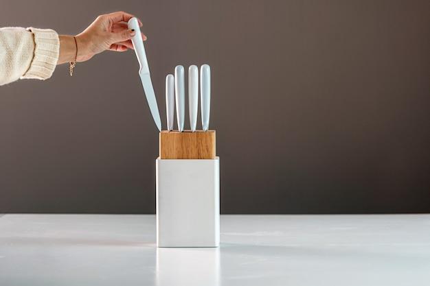 Een vrouwelijke hand neemt een mes uit de witte meshouder, keukenmes op de witte tafel