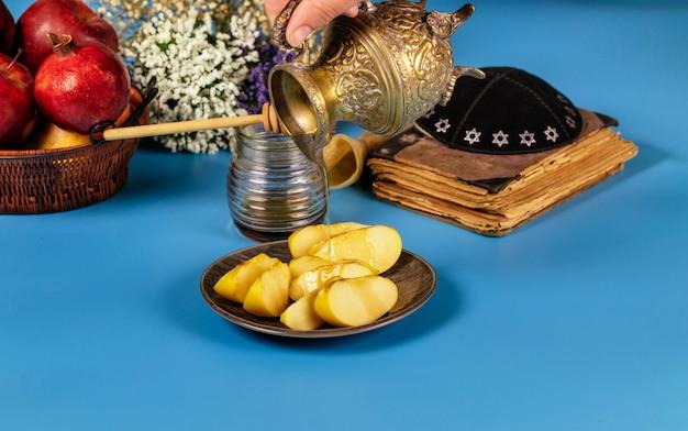 Een vrouwelijke hand neemt honing met honing voor de appelschijf en granaatappelvakantie van rosh ha shana