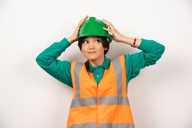 Een vrouwelijke ingenieur die een helm op witte achtergrond houdt. hoge kwaliteit foto