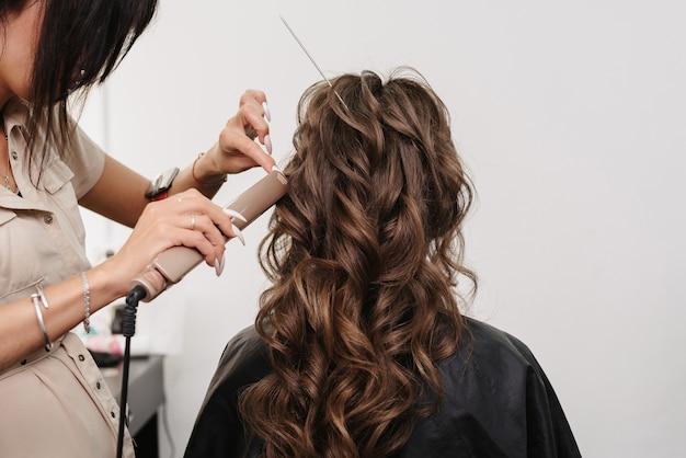 Een vrouwelijke kapper maakt bruidkapsel
