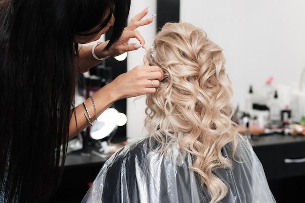 Een vrouwelijke kapper maakt een feestelijk kapsel voor een blonde in een schoonheidssalon.
