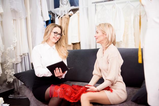 Een vrouwelijke kleermaker maakt aantekeningen in een notitieboekje over de wensen van de klant voor een nieuw pak. individueel maatwerk.