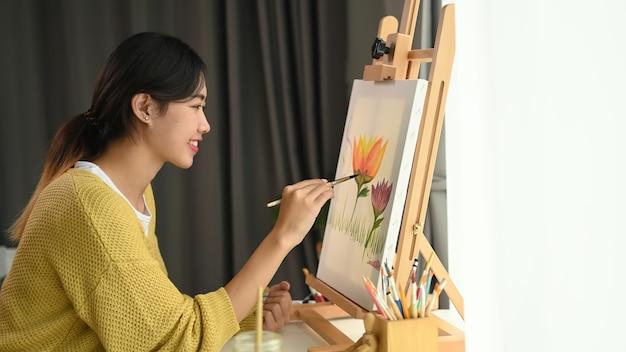Een vrouwelijke kunstenaar werkt aan het schilderen in een studio met helder daglicht