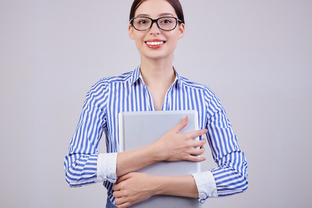 Een vrouwelijke manager kijkt recht met een glimlach in een gestreept wit-blauw shirt met zwarte bril en een laptop