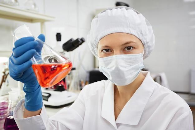 Een vrouwelijke medische of wetenschappelijke onderzoeker of een vrouwelijke arts die een reageerbuis met oplossing bekijkt