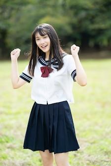 Een vrouwelijke middelbare schoolstudent poseren ondersteunend met een glimlach buitenshuis