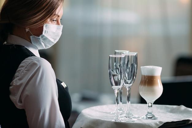 Een vrouwelijke ober met een europees uiterlijk in een medisch masker serveert latte-koffie.