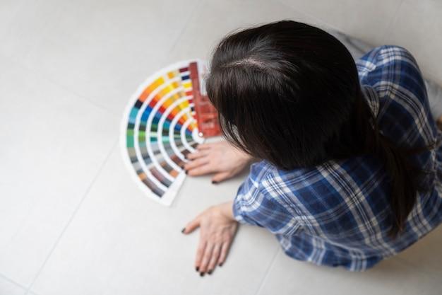 Een vrouwelijke ontwerper die een interieurkleur kiest met behulp van het kleurenpalet