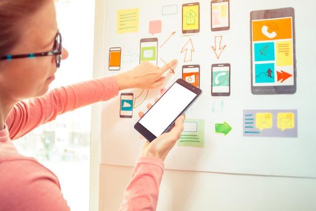 Een vrouwelijke ontwerper is een ontwikkelaar van mobiele apps die een smartphone bewaart.
