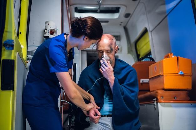 Een vrouwelijke paramedicus die eerste hulp verleent aan een gewonde man, redde uit het vuur en controleerde zijn pols