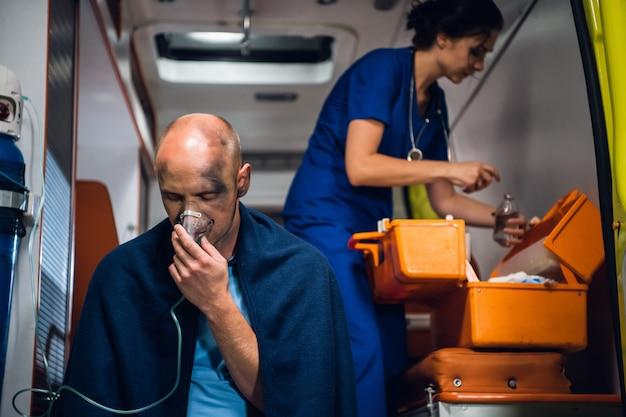 Een vrouwelijke paramedicus van dienst, met patiënt