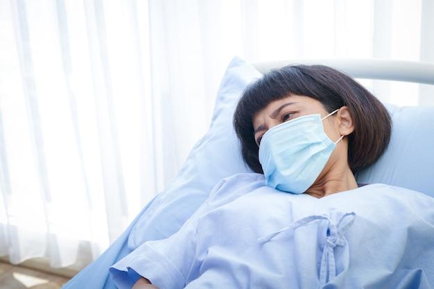 Een vrouwelijke patiënt met een masker ligt op een ziekenhuisbed. behandeling van patiënten tijdens de coronavirusepidemie