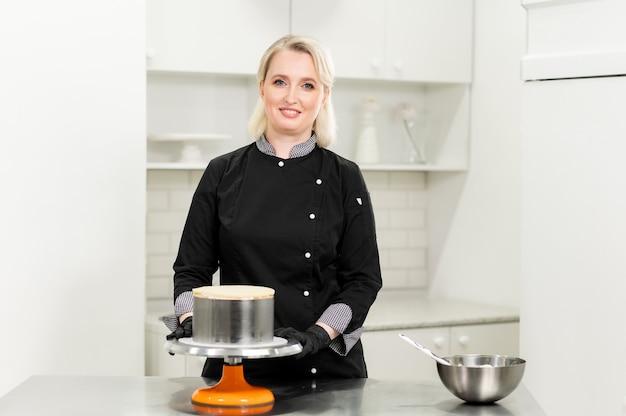 Een vrouwelijke patissier bereidt een cake en zichzelf in de keuken