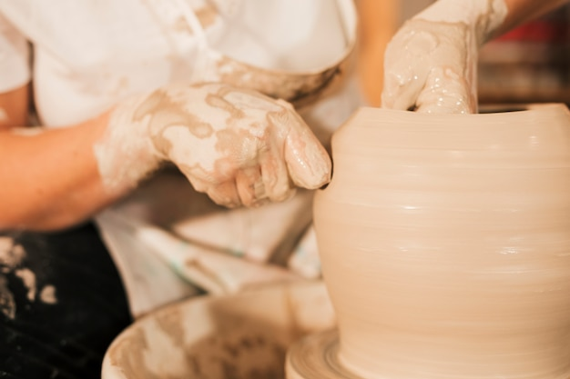 Een vrouwelijke pottenbakker werkt aan het maken van een aarden pot aan het pottenbakkerswiel