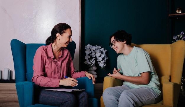 Een vrouwelijke psycholoog en een tienerpatiënt zitten in stoelen op kantoor en hebben een gesprek
