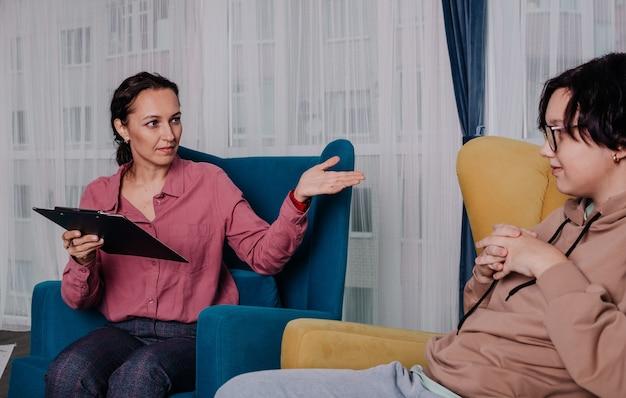 Een vrouwelijke psycholoog heeft een kantoorafspraak met een tienerpatiënt