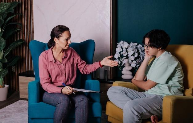Een vrouwelijke psycholoog ontvangt een tienermeisje op kantoor