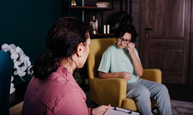 Een vrouwelijke psycholoog zit in een stoel en raadpleegt een huilend tienermeisje
