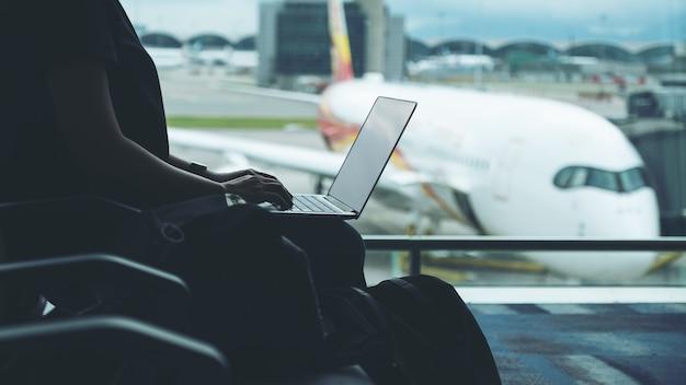 Een vrouwelijke reiziger die een laptop gebruikt terwijl hij op de luchthaven zit