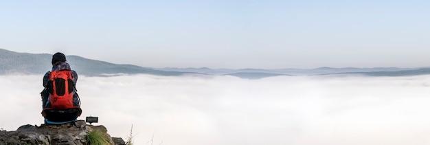 Een vrouwelijke reiziger in de bergen zit aan de rand van een klif en bewondert een mistige ochtend in de mo...