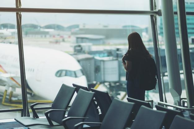 Een vrouwelijke reiziger met rugzak op de luchthaven