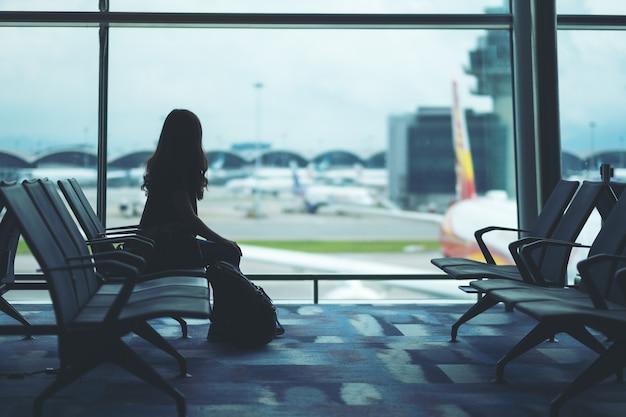 Een vrouwelijke reiziger met rugzak zit en wacht op de luchthaven