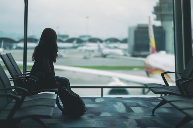Een vrouwelijke reiziger zit en wacht met rugzak op de luchthaven