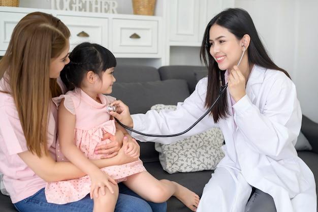 Een vrouwelijke stethoscoop van de artsenholding onderzoekt een gelukkig meisje in het ziekenhuis met haar moeder, medisch concept