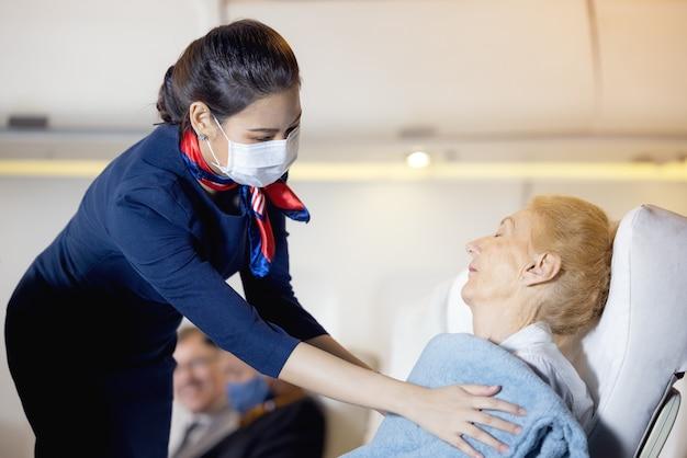 Een vrouwelijke stewardess kleedde een oudere passagier die op de passagiersstoel lag te slapen