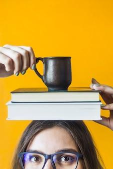 Een vrouwelijke student die een bril draagt houdt een stapel boeken en een kopje koffie op haar hoofd