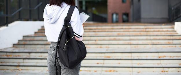 Een vrouwelijke student met een zwarte rugzak en een notitieboekje in haar handen staat op de trap voor de universiteit. hoger onderwijs, het begin van het schooljaar, terug naar school. copyspace
