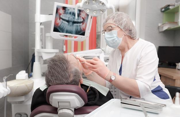Een vrouwelijke tandarts behandelt de tanden van een mannelijke patiënt in een modern kantoor van een tandheelkundige kliniek