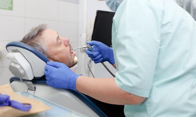 Een vrouwelijke tandarts behandelt de tanden van een mannelijke patiënt in het kantoor van een tandheelkundige kliniek