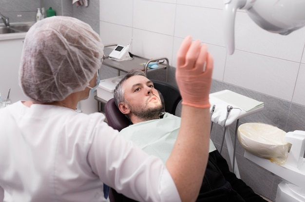 Een vrouwelijke tandarts bereidt zich voor om een mannelijke patiënt in het kantoor van een tandheelkundige kliniek te onderzoeken