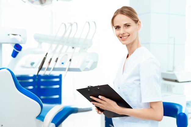 Een vrouwelijke tandarts houdt tablet voor papieren.