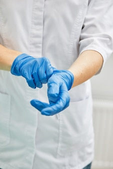 Een vrouwelijke tandarts zet handschoenen aan tegen een achtergrond van tandheelkundige apparatuur in een tandartspraktijk
