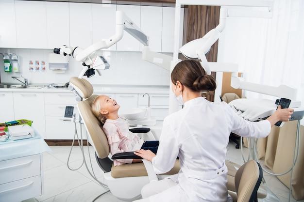 Een vrouwelijke tandarts zit naast het meisje en probeert een contact met haar op te zetten om haar voor de controle te troosten.