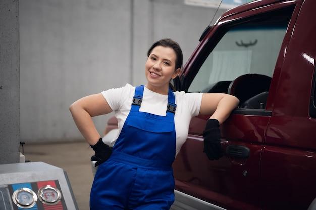 Een vrouwelijke techneut in blauwe overall staat bij de auto