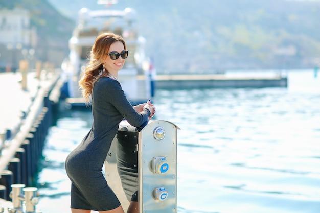Een vrouwelijke toerist staat in de buurt van de rivier en wacht op de landing op een jacht