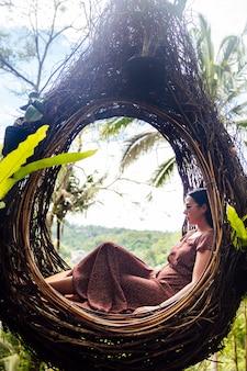 Een vrouwelijke toerist zit op een groot vogelnest op een boom bij ba