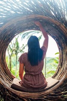Een vrouwelijke toerist zit op een groot vogelnest op een boom op het eiland van bali
