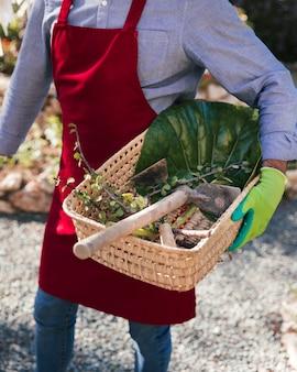 Een vrouwelijke tuinman die mand met schoffel en geoogst takje houdt