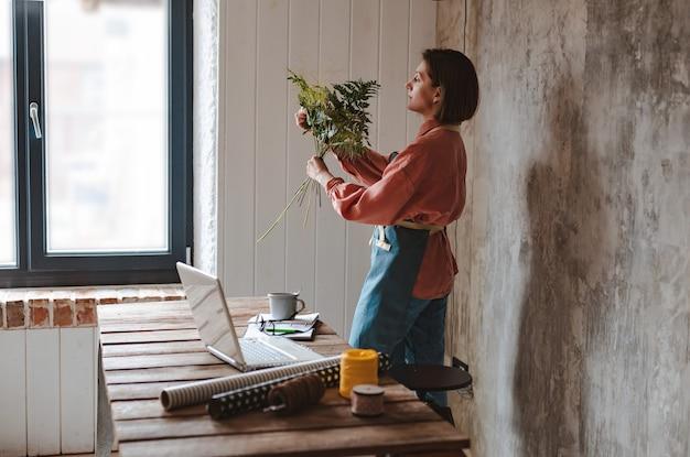 Een vrouwelijke tuinman met een bril en een schort met een plant op kantoor