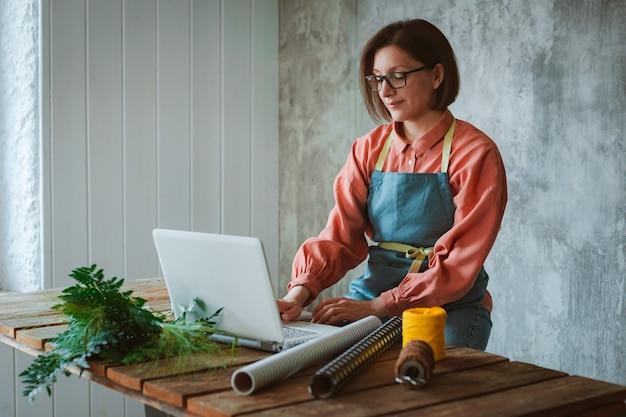Een vrouwelijke tuinman met een bril en een schort, zittend aan een houten tafel tegen een betonnen plaat, met behulp van een laptop om te werken