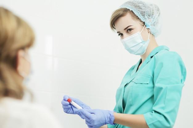 Een vrouwelijke verpleegster in een medisch masker houdt reageerbuizen voor een bloedonderzoek