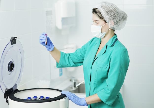 Een vrouwelijke verpleegster of arts in een medisch masker houdt een reageerbuis vast voor een bloedtest. laboratoriumcentrifuge voor het scheiden van bloedbestanddelen
