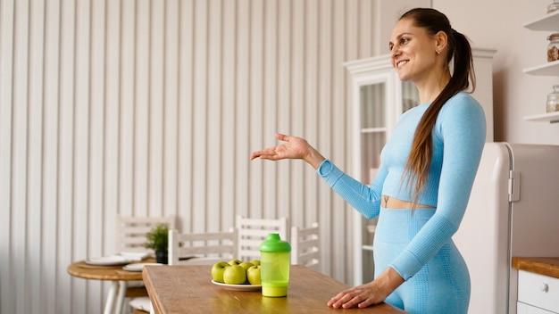 Een vrouwelijke voedingsdeskundige vertelt in de keuken over de voordelen van gezonde voeding. zijaanzicht. gezonde levensstijl vloggen of seminarconcept